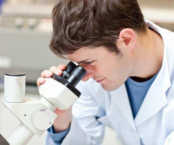 Смотрит в микроскоп
